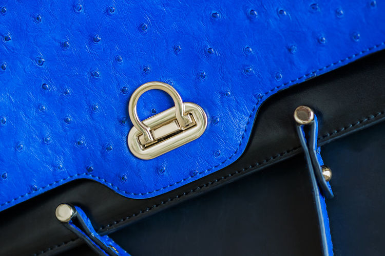 Close-up texture of vivid fashion blue color handbag from genuine leather with embossed under the skin of Ostrich, gold lock. Concept of shopping, manufacturing, lifestyle Luxury Blue Metal Close-up High Angle View Texture Leather Handbag  Genuine Detalles Fashion Violet Shopping Manufacturing Hands Ostrich Macro Clasp Metallic Lock Detail