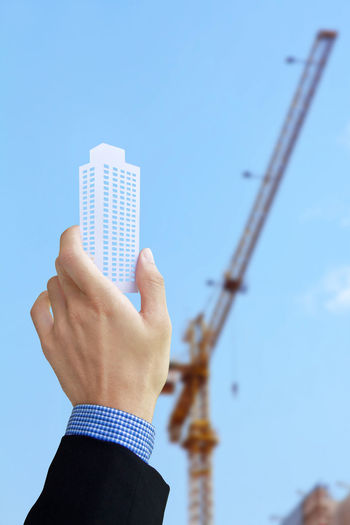 Close-up of hand holding construction site against clear blue sky