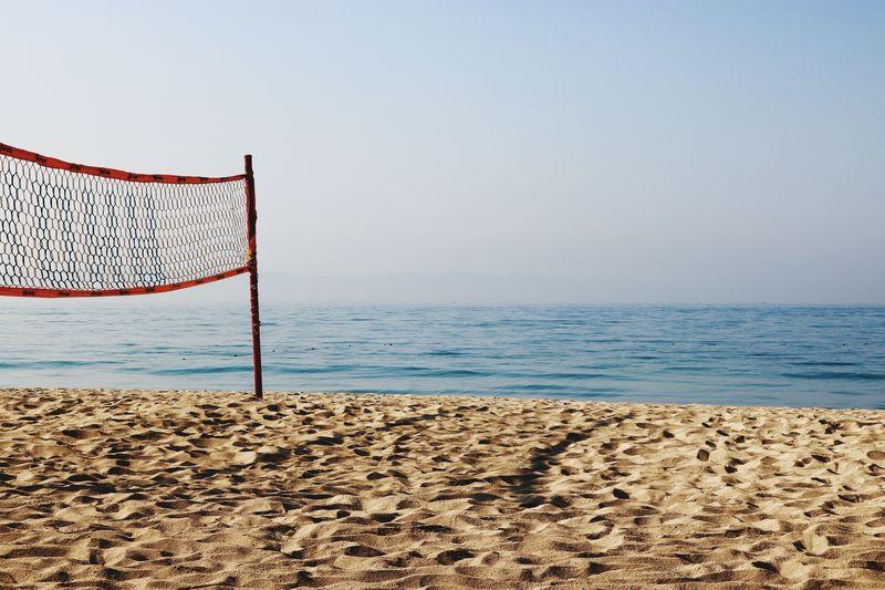 Net on shore at beach against sky