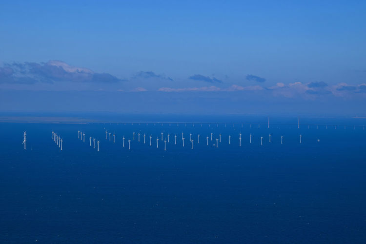 Windmills in sea against sky