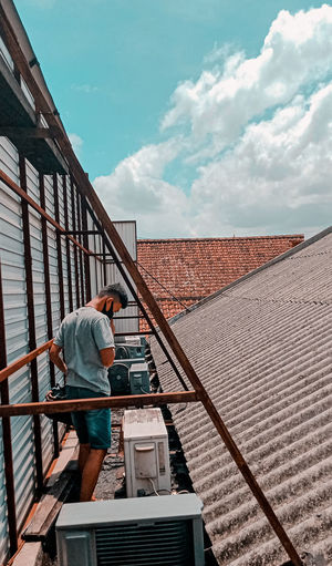 Side view of man working on railing against sky