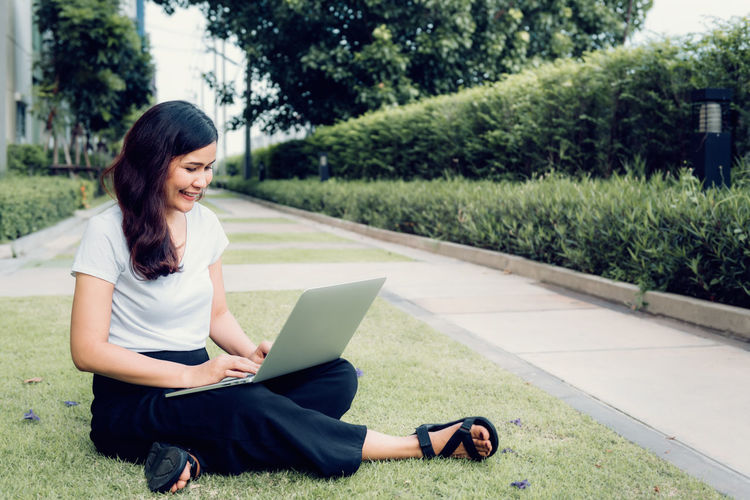 Portrait of young woman using laptop and sitting on garden grass. Real People Sitting Laptop Using Laptop One Person Young Adult Plant Young Women Grass Technology Leisure Activity Full Length Casual Clothing Connection Adult Computer Women Lifestyles Wireless Technology Smiling Outdoors