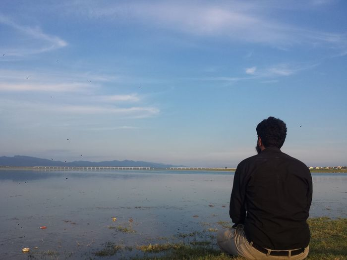 Rear view of man looking at sea against sky