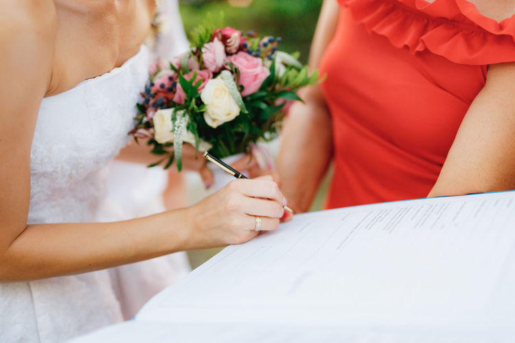 Midsection of woman holding bouquet