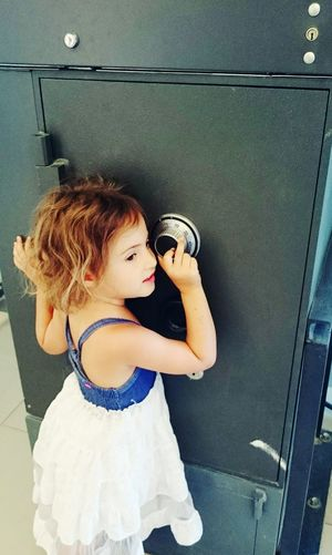 Cute girl in front of safety deposit box