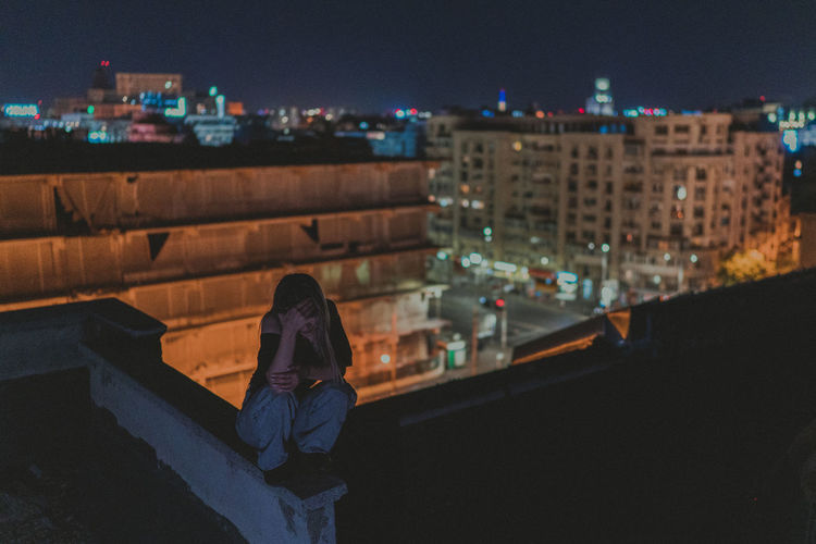 Woman sitting on retaining wall against buildings in city at night