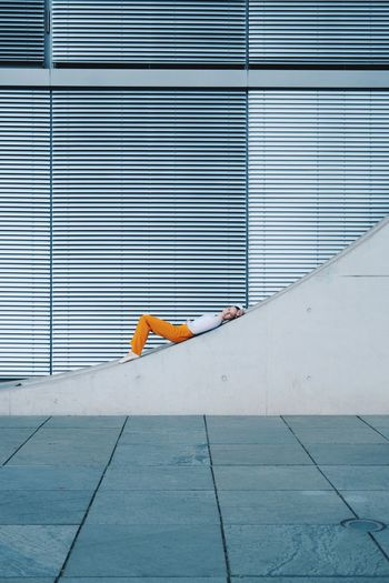 Side view of person lying on footpath against building