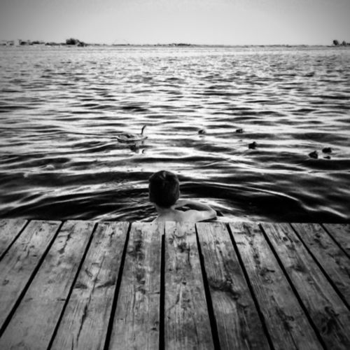 EyeEm Best Shots EyeEm Selects Water Wood - Material Sky Sea Scenics - Nature One Person Tranquility Beauty In Nature Nature Tranquil Scene Leisure Activity Rear View Real People Rippled Pier Swimming Outdoors Day Wood