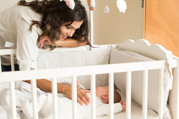 Mother Looking At Son In Crib