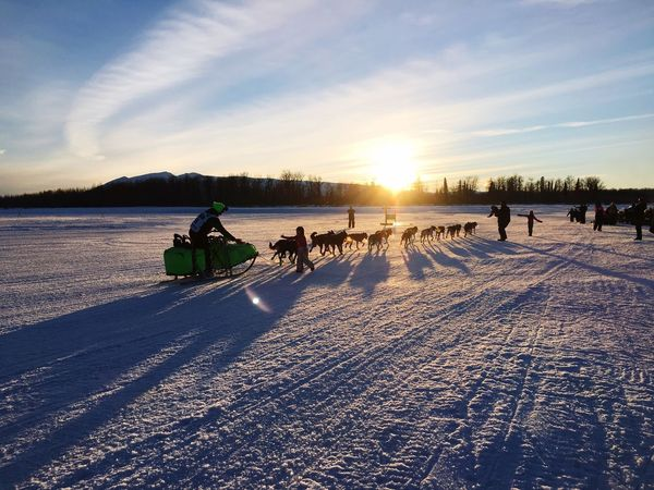 Watching the Iditarod sled dog race. Sky Real People Sunset Lifestyles Outdoors Iditarod Dog Race Iditarod Dogs Iditarod Dogs Dog Sports adventure Mushing Dog Mushing Alaskan sports Men Sunlight Leisure Activity Nature Beauty In Nature Scenics Water Togetherness Day People Adult