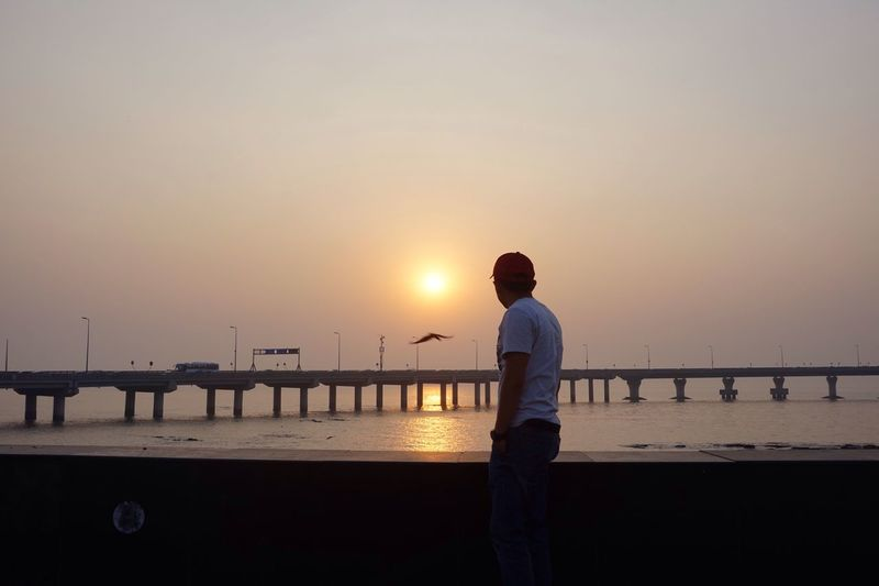 Side View Of Man Standing By Railing Against Sea During Sunset