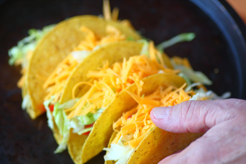 Man with several freely made tacos Baking Pan Dinner Lunch Man Tacos Textures Close-up Dark Background Day Fingers Food Grated Cheese Hand Healthy Eating Holding Home Cooking Indoors  Lettuce Mexican Food One Person People Ready-to-eat Supper Taco Night Tasty