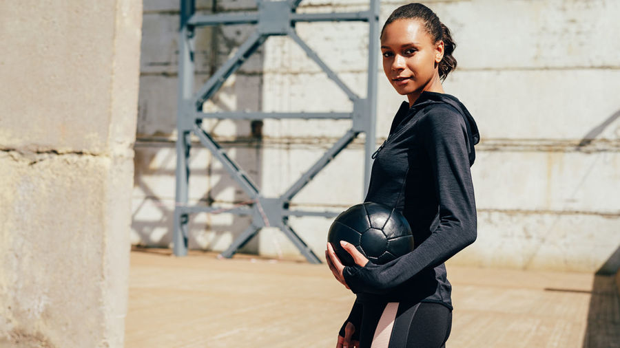 Portrait Of Young Woman With Ball Standing Against Wall