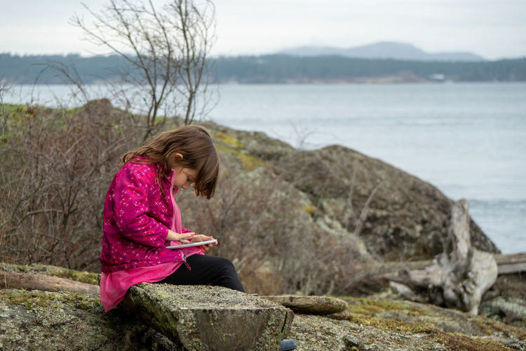 Rear view of girl sitting on rock