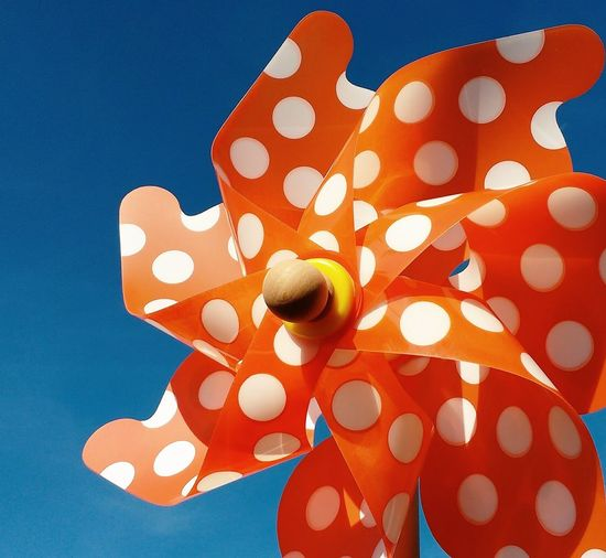 Close-Up Of Orange Pinwheel With Polka Dots Against Clear Sky