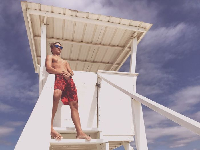 Low Angle View Of Shirtless Young Man Standing At Lifeguard Hut