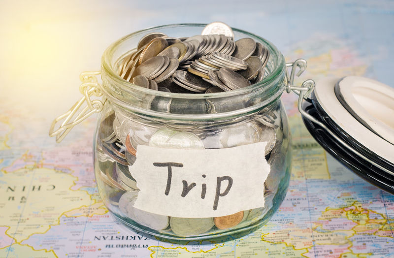 Close-Up Of Coins In Jar With Trip Text On Map