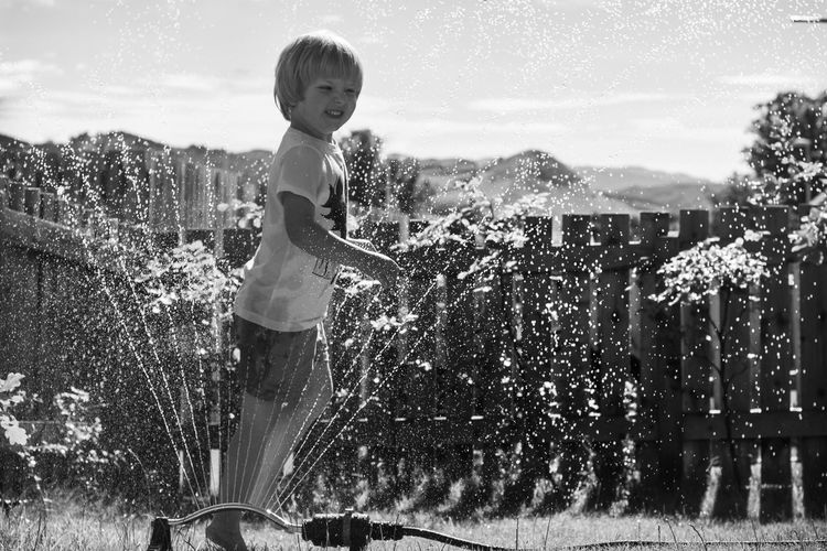 Playful boy enjoying in sprinkler
