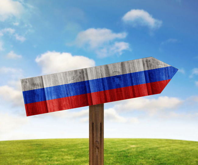 Close-up of russian flag painted on wooden sign against sky