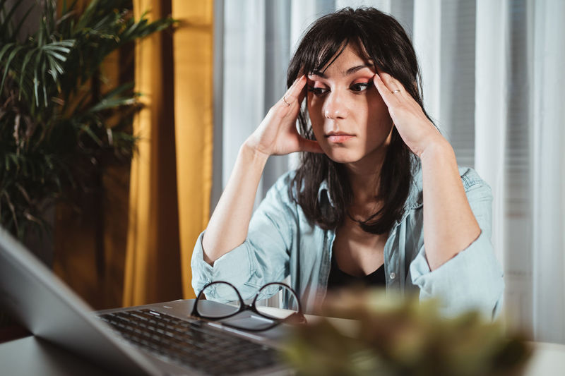 Frustrated young woman by laptop in office