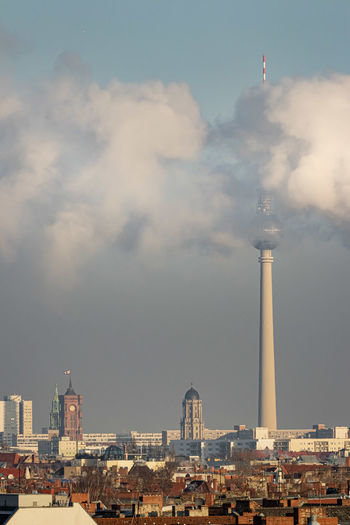 Fernsehturm covered with smoke against sky