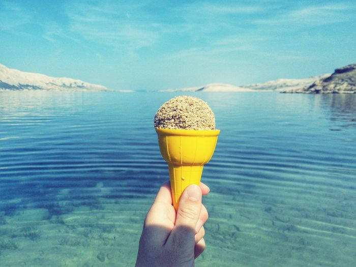 Cropped Image Of Hand Holding Ice Cream By Sea Against Sky