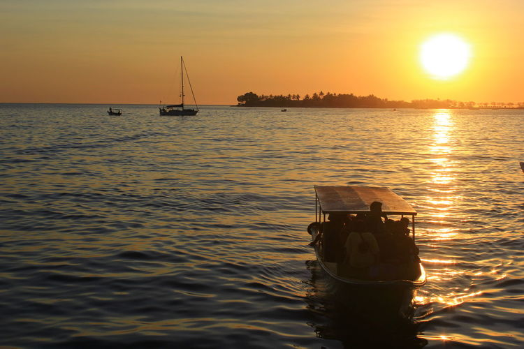 the sun sets on the edge of the city of Makassar Sunset Water Sky Nautical Vessel Beauty In Nature Sea Sun Scenics - Nature Orange Color Mode Of Transportation Reflection Transportation Waterfront Nature Silhouette Idyllic Sunlight Tranquility Men Outdoors Horizon Over Water Sailboat