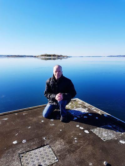Full length of man kneeling on pier against blue sky