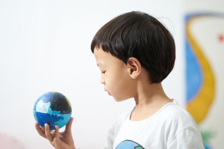 Cute boy holding globe