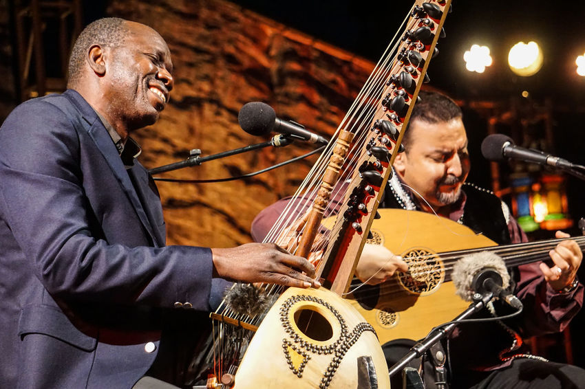 """The Fes Festival of World Sacred Music 2018: a traditional, multicultural, dazzling, entrancing display of musical disciplines from across the hundreds of musicians completely devoted to their craft, they educated audiences about their cultural history with an array of instruments, traditional costumes, and impressive vocal techniques, ranging in genre from classical to rock to Gregorian chants to laughed, cried, danced, and gave standing was an absolute privilege to photograph such a spectacle, and to feel such ancestral passion and heart radiating from the one audience member put it, """"They play for God."""" Classical Music Dance Music Singing Stage The Photojournalist - 2018 EyeEm Awards Traditional Clothing World Music Arts Culture And Entertainment Concert Fes Festival Focus On Foreground Front View Gospel Instruments Musicians Performance Profile View Real People Rock Music Trance"""