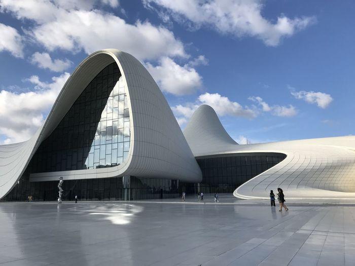 People walking in museum against sky in city