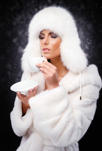 Young Woman In Fur Coat Holding Cup And Saucer Against Wall