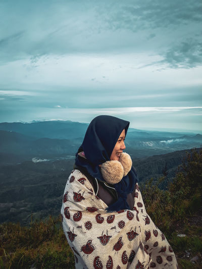 Woman wrapped in blanket looking away while standing against mountains