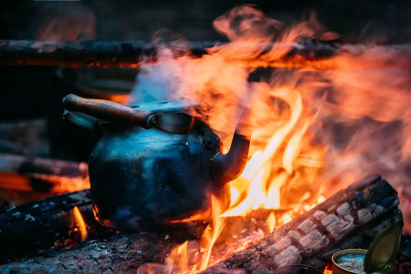 Black Old Retro Iron Camp Kettle Boiling Water On A Fire In Forest. Bright Flame Fire Of Bonfire At Dusk Night. Cooking Flame Iron Kettle Retro Smoke Black Boiling Bonfire Close-up Dusk Fire Flame Food Food Stories Forest Heat - Temperature Night Old Outdoors Vintage Water Camp Modern Hospitality