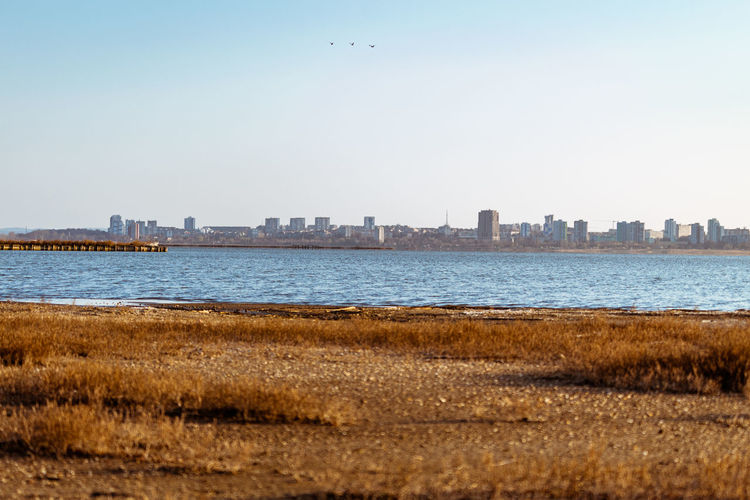 Scenic view of sea and buildings against clear sky