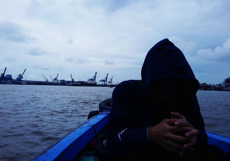 Portrait of man in boat against sky
