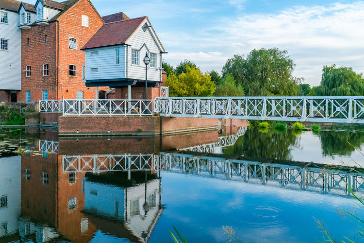 Bridge over river by house against sky