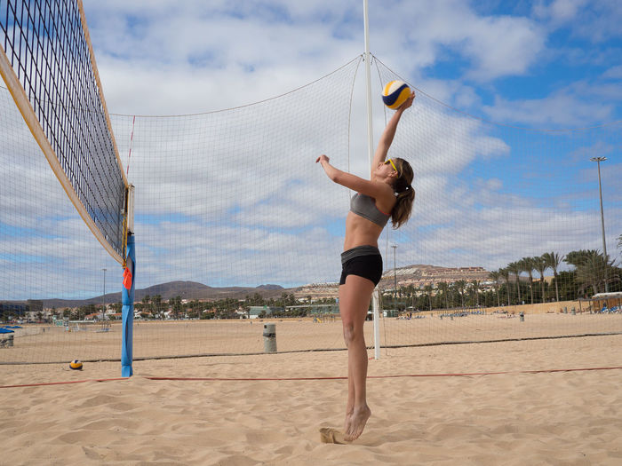 Attractive sporty young woman is jumping and smashes the volleyball over the net Fitness, Activity Attack, Attaktive, Ball Beach Beach Volleyball Beachball Bump Dig Female, Full Length Hit Jump Matches Net Outdoor Outdoors Play Recreation, Smash  Sport Sportswear, Volleyball Woman