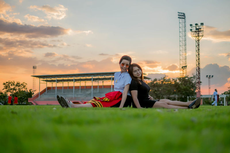 Portrait of smiling young women sitting on grass during sunset