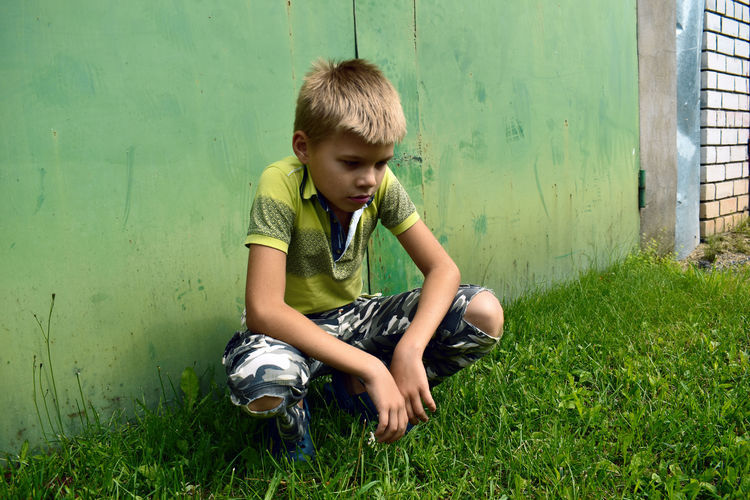 Boy crouching on grass against wall at park