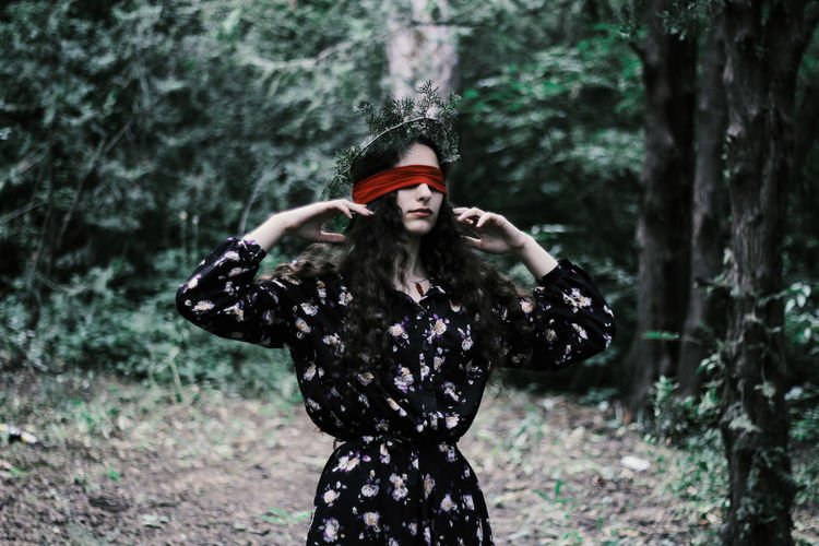 Fashionable Young Woman With Blind Fold While Standing In Forest