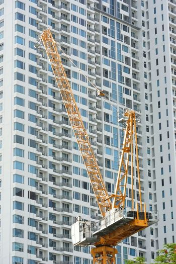 Low Angle View Of Crane Against Incomplete Skyscraper
