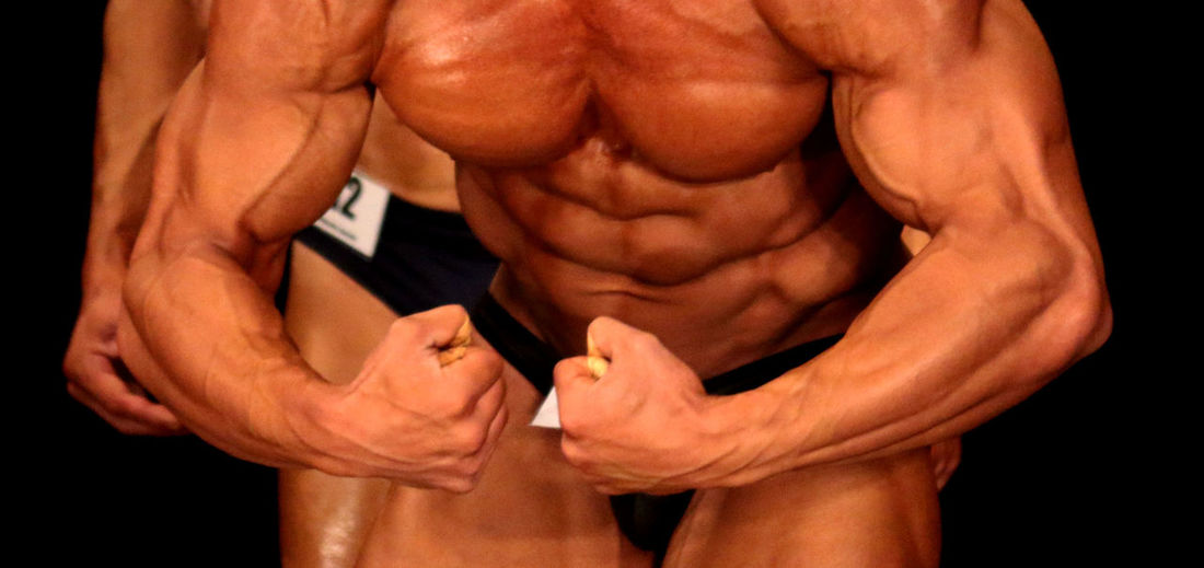 Mid Section Of An Athlete Flexing Muscles