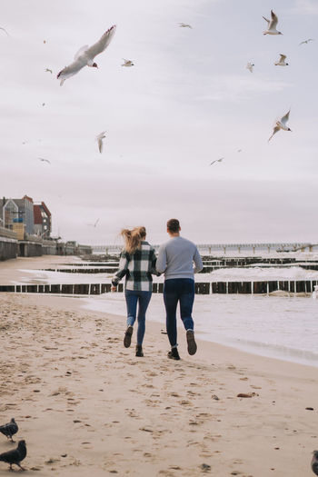 Close up of couple running near the sea and looking to each other.