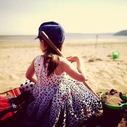 Rear view of girl sitting at beach against sky during sunny day