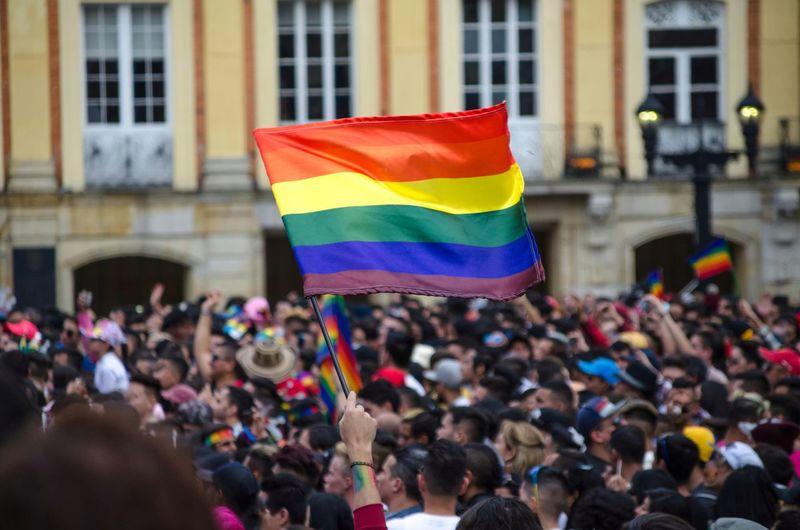Rainbow Flag In Crowd Against Building