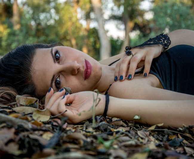 Portrait of beautiful young woman lying on field