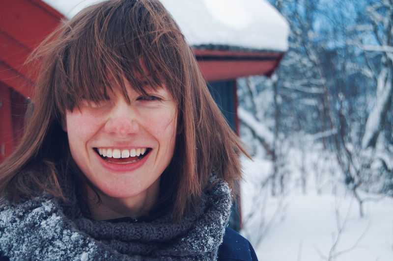 Close-Up Portrait Of Smiling Young Woman Against Snow