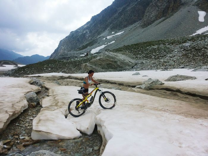Full length of woman walking with mountain bike on snow against mountains