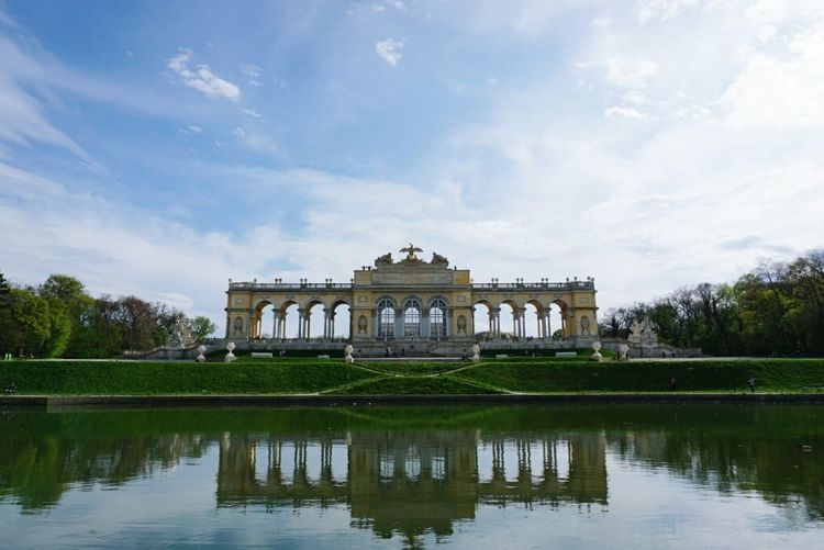 Schonbrunn palace reflecting in lake against sky
